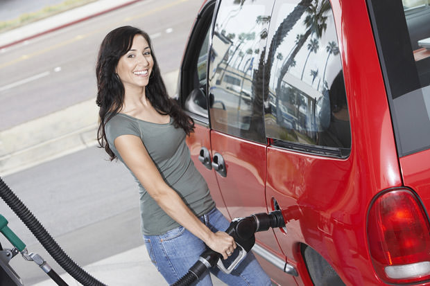 bigstock-Happy-woman-refueling-her-car-36428608
